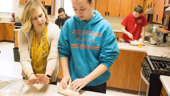 Pulaski High School family and consumer science teacher Liz Moehr, left, instructs Emily Perrault in the correct way to hand roll dough for a flatbread.