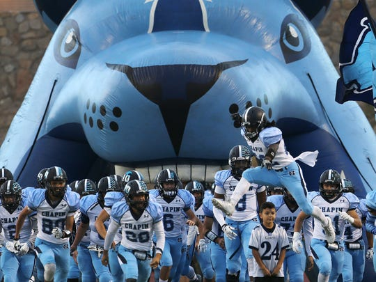 Chapin's Mondarius Johnson, lower right, leaped over a young boy, as the Huskies took the field Thursday.