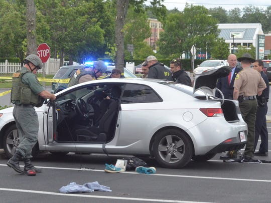 Police investigate a Kia sedan that was the site of a pipe bomb explosion June 8, 2016, on the road before pulling into the Shelburne Road Plaza parking lot in Burlington.
