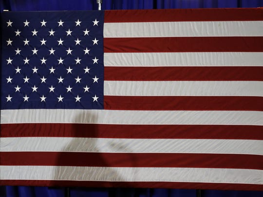In this Aug. 31, 2018, file photo, President Donald Trump's shadow is shown on an American flag as he speaks before signing an executive order at the CPCC Harris Conference Center in Charlotte, N.C. A majority of Americans disapprove of the way President Donald Trump is handling U.S. foreign policy and about half think the country's global standing will deteriorate during the next year, according to new poll about the state of the nation's affairs with the world.