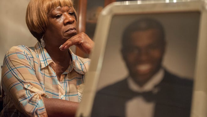 Brenda Macklin of Camden, whose oldest son, Rashay, was found shot dead in a burned-out Camden apartment 14 years ago, sits by a photo of him.  She is confident someone knows something about the killing. Find out more about the cold case Tuesday.