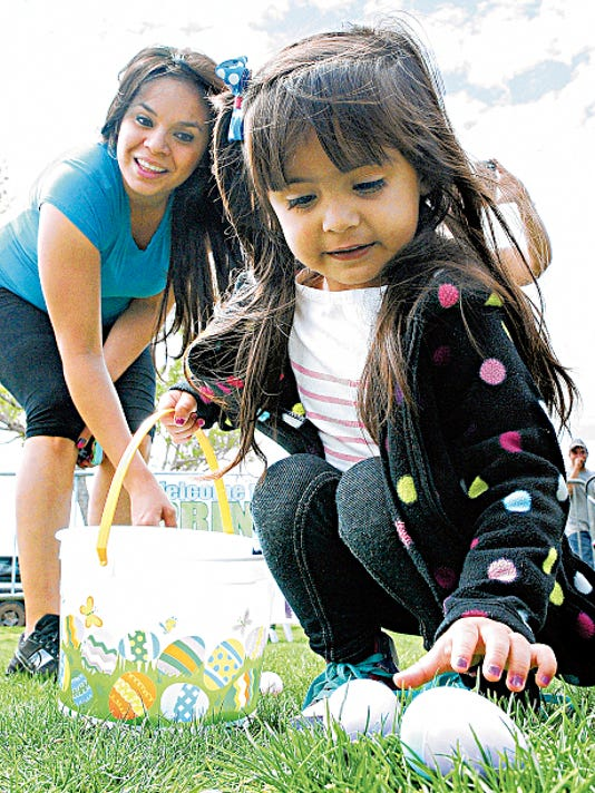 Jaeda Urbina, 3, of Las Cruces, fills her basket during the last year's Springfest egg hunt while her mother, Diana Alarcon, cheers her on in the background. This year's event is set for Saturday at Young Park.