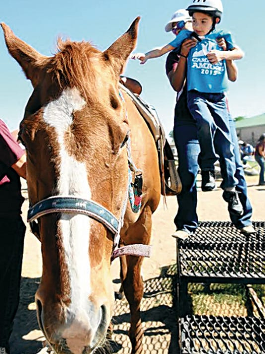 Deanna Duran helps Josh Velasquez, a Camp New Amigos participant, up on to a horse from NMSU Therapeutic Riding Program.