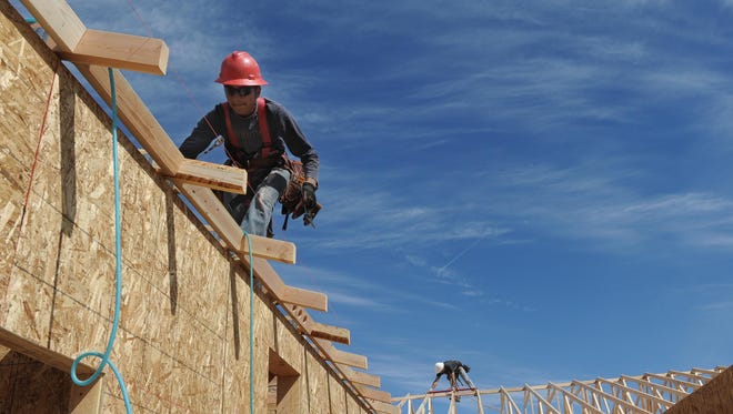 Rueben Perez carefully walks along a roof in 2013 while framing a new house in northwest Reno.