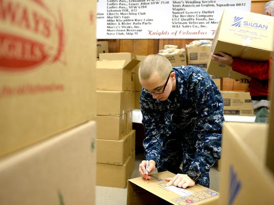 Artur Samarin, 23, posed as Asher Potts, 17, and a Harrisburg High School junior and ROTC, NJROTC and Sea Cadet in this file photo as he helped organize boxes at the annual food drive at the Navy Club in Lebanon on Thursday, Dec. 18, 2014.