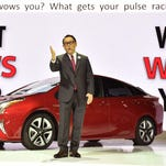 Toyota President Akio Toyoda delivers a speech in front of the company's next generation hybrid vehicle Prius during a briefing at the Tokyo Motor Show on Wednesday. The Tokyo show kicked off on with a focus on cars that drive themselves, eco-friendly technologies.