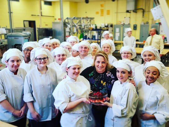 Courier-Post reporter Carly Q. Romalino poses with Gloucester Co. Institute of Technology's culinary arts students who taught her how to make the chocolate-strawberry cake in a live Facebook broadcast Feb. 10, 2017.