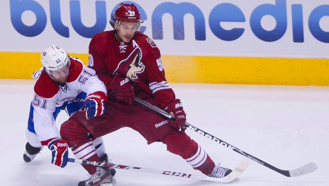 The Coyotes' Antoine Vermette keeps the puck away from the Canadiens' David Desharnais in the first period on March 6, 2014.