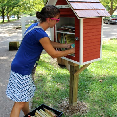 Holly Bennett stocks a little free library with books