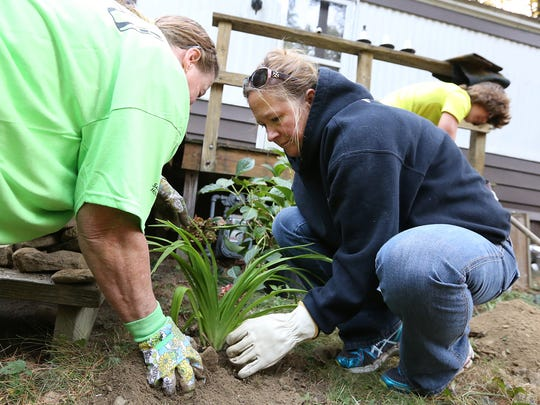 Debra Rethmel, of Cohochton, and Lisa Fields, of Prattsburgh, secure a plant outside Roger Cox's Painted Post home Saturday.