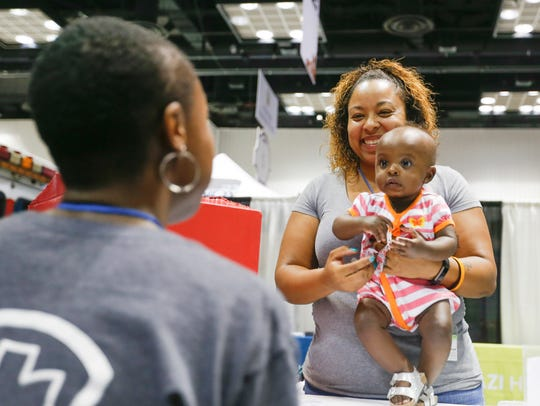 Tamar Francis, left, talks to Chrisney Ball and 6-month-old