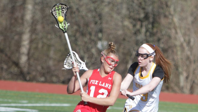Fox Lane's Lindsay West attempts to drive past Mahopac's Alyssa Kirby during a Section 1 girls lacrosse game between Mahopac and Fox Lane at Mahopac High School on Friday, April 15th, 2016. Mahopac won in overtime 9-8.