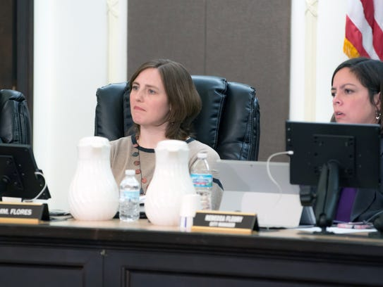 Battle Creek Commissioner Kate Flores, center, listens