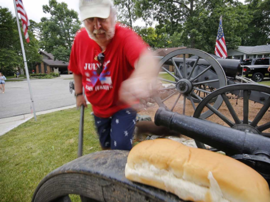Frank Markel reaches for a hotdog bun he is using as wadding as he prepares one of four cannons Makel owns to fire in the front yard of his house, 4004 Shady Lane Court, July 4, 2016, in Greenfield.