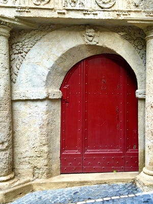 One of the most beautiful doors in Pézenas, France, is painted bright red and framed by a carved stone arch and columns.