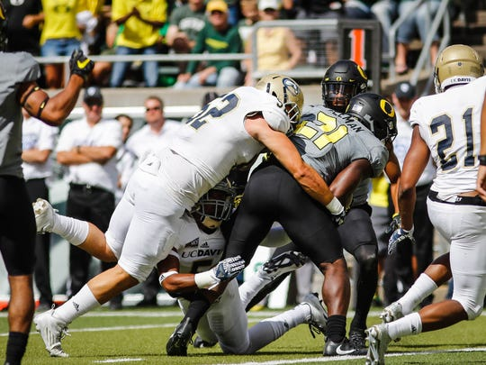 Oregon Ducks running back Royce Freeman (21) scores a touchdown after breaking a tackle from UC Davis linebacker Brady Stibi in the first quarter of an NCAA college football game in Eugene, Ore., Saturday, Sept. 3, 2016.