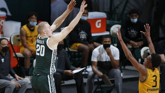 Michigan State's Joey Hauser, left, shoots against Oakland's Micah Parrish (3) during the first half of an NCAA college basketball game, Sunday, Dec. 13, 2020, in East Lansing, Mich.