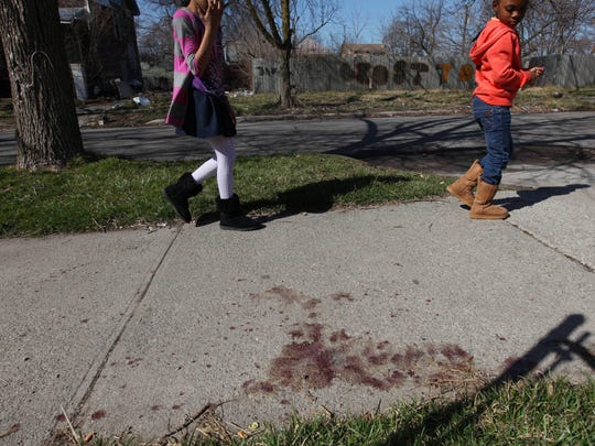 After Michael Green was shot playing basketball near his Detroit home, the sidewalk was stained with blood. Two schoolchildren walk by it on March 14, 2012, on their way to the corner store. Green is featured in Aftermath, a podcast about gunshot survivors in America. SUSAN TUSA\Detroit Free Press