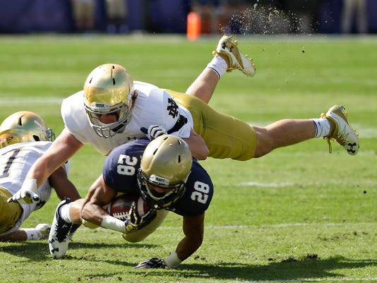 """FILE - In this Nov. 5, 2016, file photo, Notre Dame linebacker Greer Martini, top, brings down Navy running back Dishan Romine (28) after a short gain during the first half of an NCAA college football game in Jacksonville, Fla. Notre Dame's turnaround season took a detour last week. The ninth-ranked Fighting Irish have no time to wallow in misery, either, not with Navy visiting on Saturday. """"You got to be at the right place in the right timing against an offense like this and if you're not, they exploit you,"""" senior linebacker and captain Greer Martini said. (AP Photo/John Raoux)"""