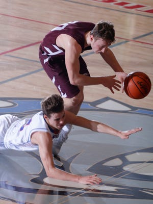 Mason's Travis Mussell, left and Eaton Rapids' Drew Shafer dive for the ball Tuesday, Feb. 21, 2017, in Mason, Mich.