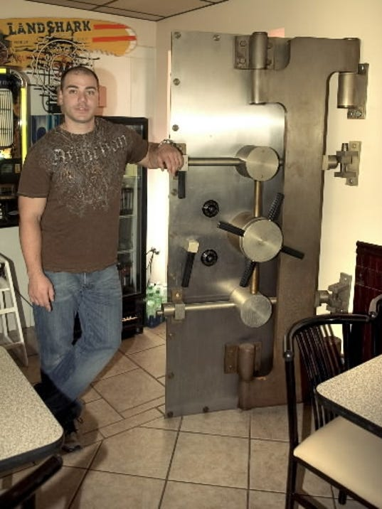 Athan Margetas poses with the building s original bank vault door, which was moved for decorative impact. The Vault Pizza & Deli was a bank before Margetas purchased it in 2003.
