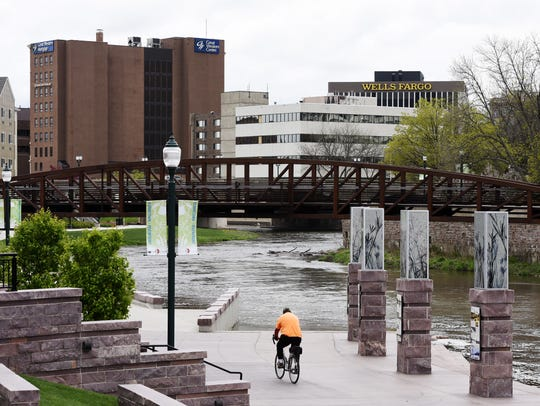 A bicycle rider travels along the River Greenway downtown.