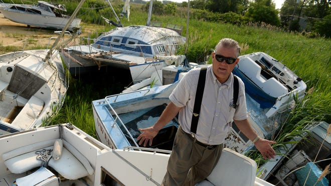 Greenwich Marina and Boat Works owner Marvin K. Hitchner III stands with a pile of boats Wednesday that were ruined by Superstorm Sandy. The marina recently received $10,000 in grant money to help its rebuilding effort.