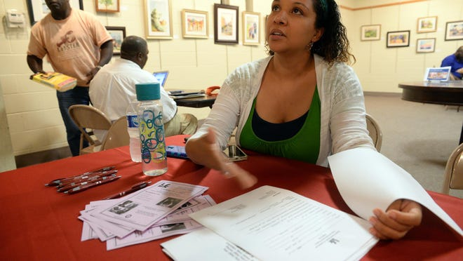 Harnel Paraison of the Hispanic Family Center of Southern New Jersey explains the organization's career plan packet at Vineland Library, Tuesday, Aug. 25, 2015.