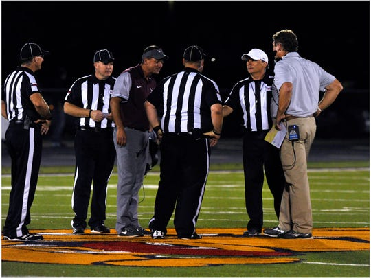 Brownwood High School head coach Kyle Maxfield (left) and Wylie High School head coach Hugh Sandifer watch as game officials flip a coin to determine who starts first during overtime at Friday's game Oct. 13, 2017. Brownwood went first, but Wylie ultimately won the game, 45-38.
