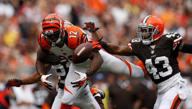 Cincinnati Bengals wide receiver Mohamed Sanu (12) is defended by Cleveland Browns strong safety T.J. Ward (43) and cornerback Buster Skrine (22) during the second quarter at FirstEnergy Stadium.