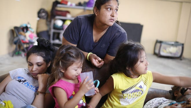 A migrant mother who is waiting to seek asylum for herself and her two daughters in the U.S., gathers with another migrant in a shelter for migrant women and children in Tijuana, Mexico.