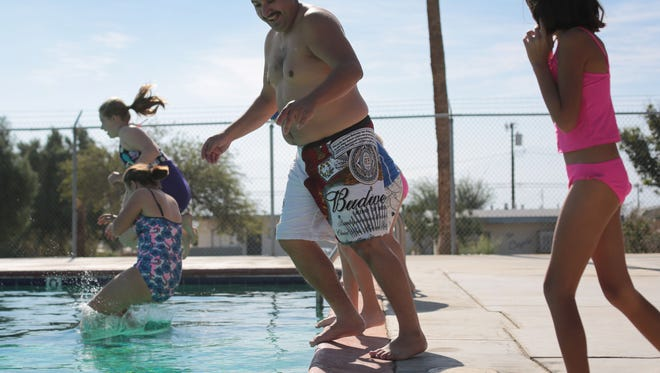 In this photo Danny Campos of Desert Hot Springs and his daughter Olivia Campos, 8, take a plunge at Wardman Park in Desert Hot Springs, on Saturday, November 15, 2014.