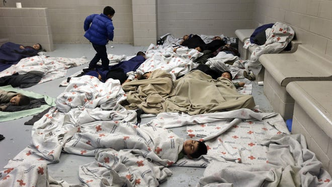 In this June 18, 2014, file photo, detainees sleep in a holding cell at a U.S. Customs and Border Protection processing facility in Brownsville,Texas. For nearly two months, images of immigrant children who have crossed the border without a parent, only to wind up in concrete holding cells once in United States, have tugged at heartstrings. Yet most Americans now say U.S. law should be changed so they can be sent home quickly, without a deportation hearing. A new Associated Press-GfK poll finds two-thirds of Americans now say illegal immigration is a serious problem for the country, up 14 points since May and on par with concern about the issue in May 2010, when Arizona's passage of a strict anti-immigration measure brought the issue to national prominence.