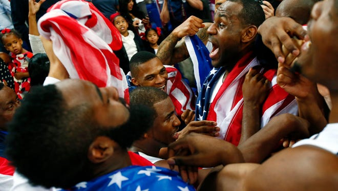 USA players including LeBron James (top right) , Chris Paul (middle) and Russell Westbrook (top) celebrate with a team huddle after defeating Spain 107-100 for the men's gold medal at the 2012 Olympics