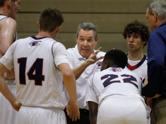 Estero boys basketball coach Lee Peters talks strategy with players during a time-out against Canterbury Wednesday in Estero.