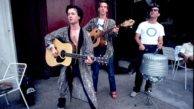 The Violent Femmes busk in Chicago in 1983. Drummer Victor DeLorenzo (right) is playing a homemade instrument, the tranceaphone.
