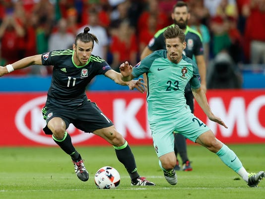 Wales' Gareth Bale, left, and Portugal's Adrien Silva fight for the ball during the Euro 2016 semifinal soccer match between Portugal and Wales, at the Grand Stade in Decines-Charpieu, near Lyon, France, Wednesday, July 6, 2016. (AP Photo/Frank Augstein)