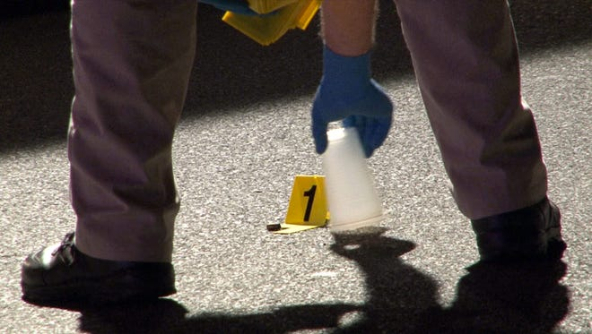 A Monmouth County investigator removes a plastic cup covering a shell casing on Coleman Avenue in Long Branch late Wednesday evening, July 22, 2015, where a multiple shooting alledgedly occurred.