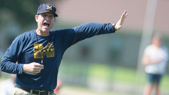 Michigan Head Coach Jim Harbaugh yells during Coach Jim Harbaugh's Elite Summer Football Camp at Prattville High School in Prattville, Ala., on Friday, June 5, 2015.