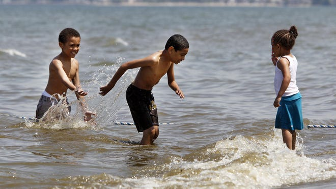 Christopher Jenkins, left, Juan Ramos of Greece, and Ashley Jenkins of Rochester, splash around in Lake Ontario during the opening day of the swimming area at Durand Eastman beach in 2010.