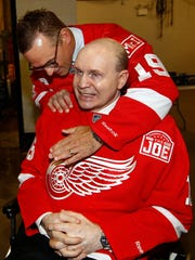 Former Red Wings captain Steve Yzerman and former Red Wing Vladimir Konstantinov, seated, embrace after a ceremony honoring Joe Louis Arena on April 9, 2017 in Detroit.