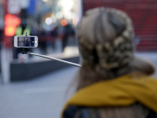 Sandy Johal uses a selfie stick to take a picture of herself in Times Square in New York, Thursday, Jan. 8, 2015. (AP Photo/Seth Wenig)