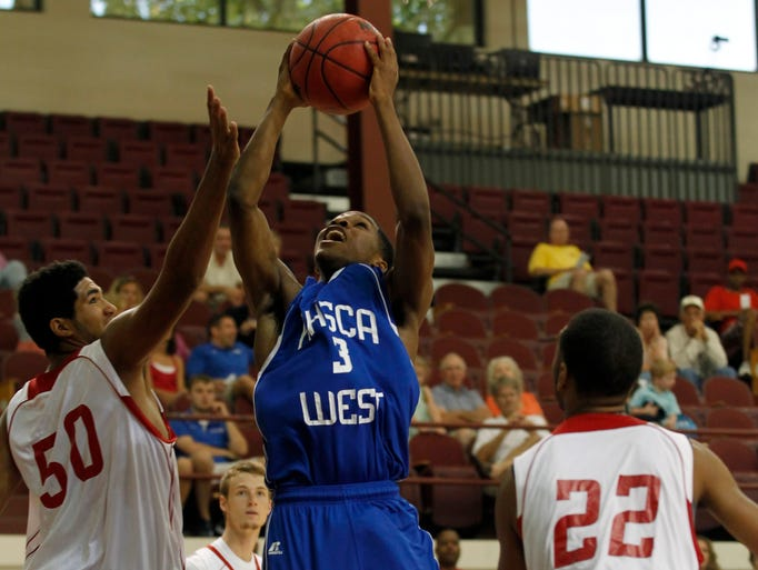 West's Eljay Cowherd (3) fights to get his shot off under pressure from East's Trey Moses (50) during the Kentucky High School Coaches Association Boys East / West Junior All-Star Basketball game at Bellarmine University in Louisville, Kentucky.       June 21, 2014