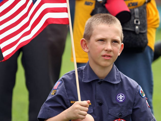 Boy Scout Liam Buddman,8, of Bridgewater, holds a flag as he listens to a presentation by William Kurzenberger from The Wallace House, who was dressed in Revolutionary War uniform. The first annual Flag Day Festival is held at Duke Island Park. Families were encouraged to show up in patriotic costumes, June 14, 2014. Bridgewater NJ. photo by Kathy Johnson  BRI 0615 Flags & Families