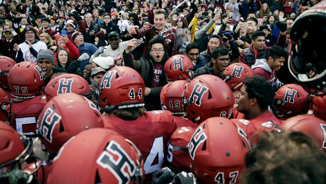 In this Nov. 17, 2018, file photo, Harvard players, students and fans celebrate their 45-27 win over Yale after an NCAA college football game at Fenway Park in Boston. Harvard defeated Yale. The Ivy League has canceled all fall sports because of the coronavirus pandemic.