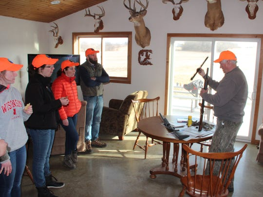 Mike Drossel, right, a volunteer with the Conservation Leaders for Tomorrow program at UW-Madison, demonstrates shotgun cleaning after a pheasant hunt.
