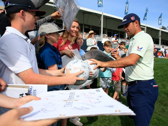 Gary Woodland signs autographs as he walks off the 18th hole during a practice round prior to the Players Championship on The Stadium Course at TPC Sawgrass  on March 11, 2020 in Ponte Vedra Beach, Florida. (Photo by Cliff Hawkins/Getty Images)