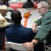 Ahmed Hassan, principal at the Islamic Center of St. Cloud, left, carries on a conversation with Dennis Konz of St. Cloud Friday during the Share Your Heritage dinner at the Islamic Center in the former Garfield School.
