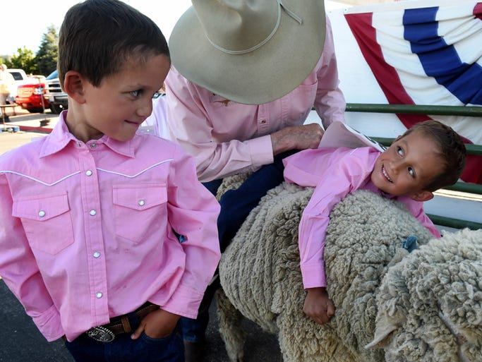 Mutton busting twins Man Munoz, 6, left, and Gabe Munoz, 6, get a little training by Gary McKay before they compete at the Reno Rodeo on Friday on June 27, 2014.