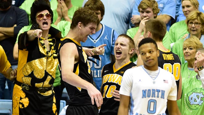 Iowa Hawkeyes guard Mike Gesell (10) celebrates with center Adam Woodbury (34) and forward Jarrod Uthoff (20) after scoring late in the second half. Iowa defeated the North Carolina Tar Heels 60-55 at Dean E. Smith Center.